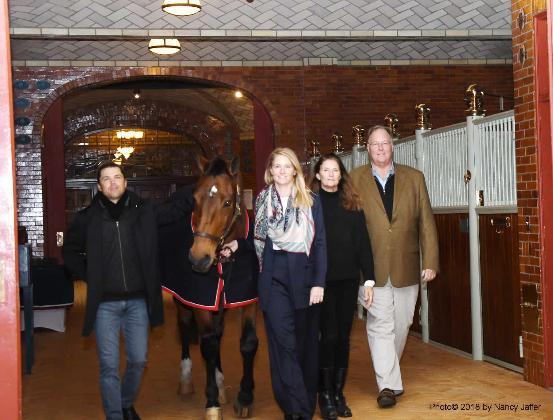 Madison on the way to her stall in the USET Foundation stable with Kent Farrington, Alexa Weeks Pessoa, and her parents, Olivia and Bill Weeks. Photo by Nancy Jaffer